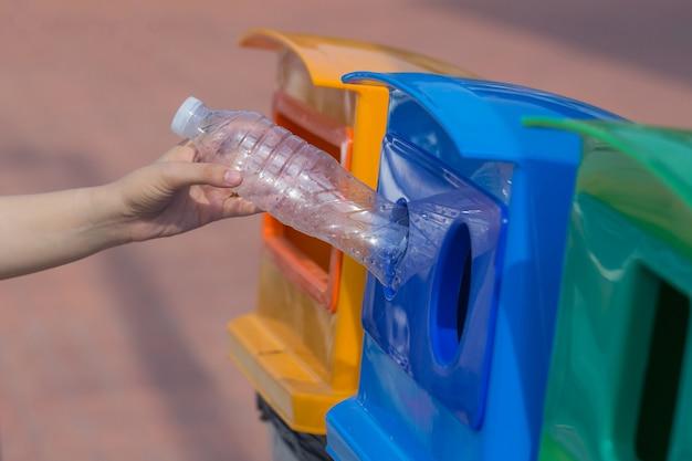 Des mains humaines jettent des bouteilles en plastique dans la mauvaise poubelle. Photo Premium
