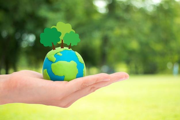 Des mains humaines, tenant des arbres de plantes sur le globe, la planète ou la terre sur fond de nature de jardin verdoyant floue. concept d'écologie. Photo Premium