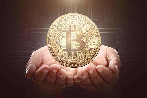 Mains humaines, tenue, bitcoin doré Photo Premium