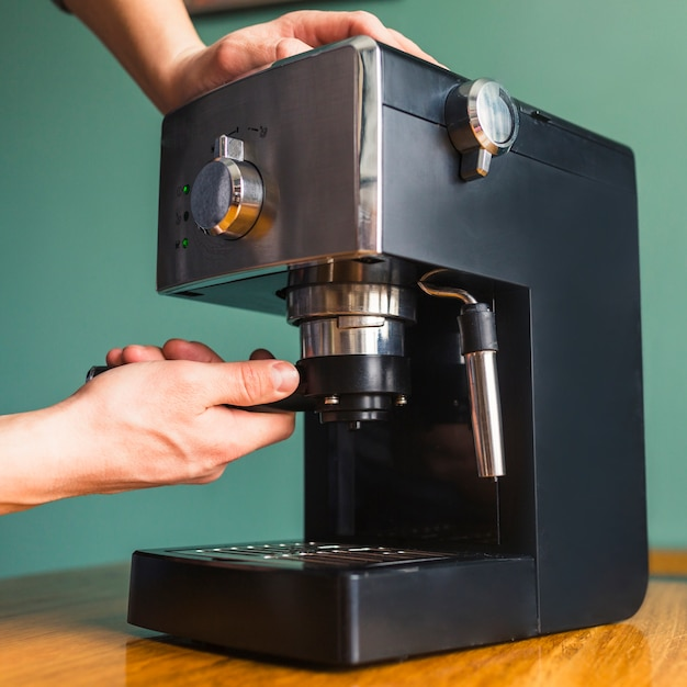 Les mains installent le filtre dans la cafetière Photo gratuit