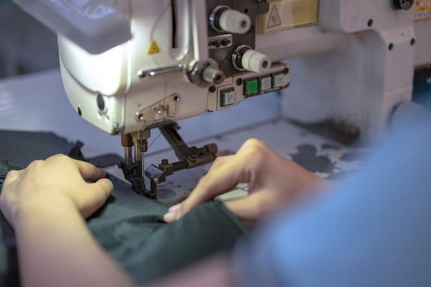 Mains De Jeune Femme Asiatique à L'aide De La Machine à Coudre En Atelier. Photo Premium