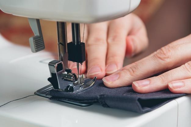 Mains de jeune fille sur une machine à coudre Photo Premium