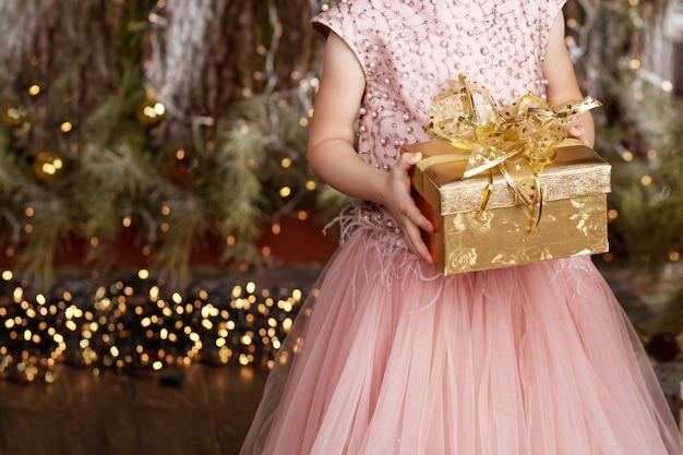 Mains de la jeune fille tenant une boîte cadeau en or. petite fille avec cadeau de noel Photo Premium