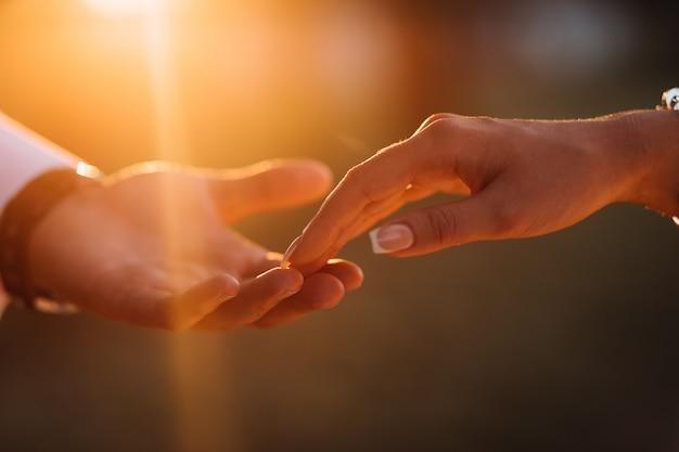 Les Mains Des Jeunes Mariés Se Touchent Affectueusement Photo gratuit