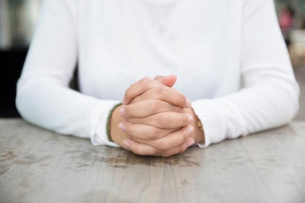 Les mains jointes de la jeune femme d'affaires assis à table Photo gratuit