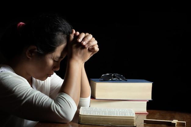 Les mains jointes en prière sur une sainte bible à l'église Photo gratuit