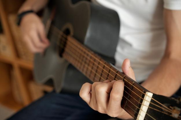 Mains jouant de la guitare Photo gratuit