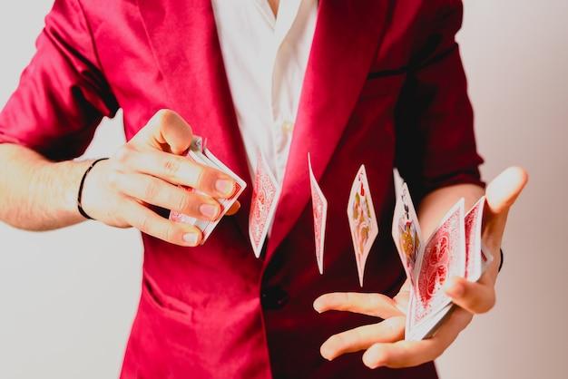 Mains de magicien faisant des tours avec un jeu de cartes. Photo Premium