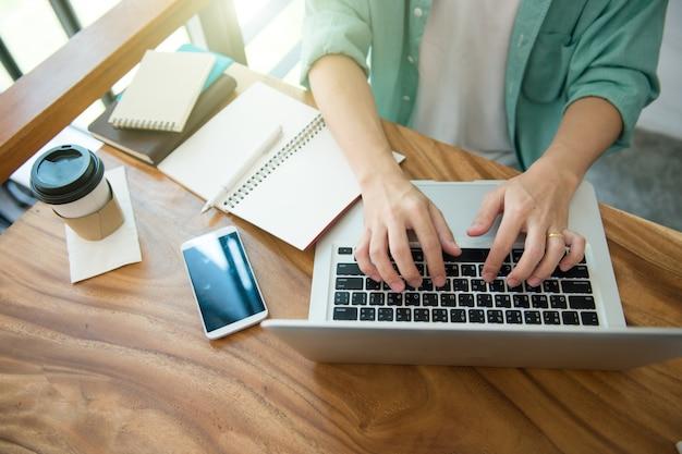 Mains mâles affaires, dactylographie, sur, a, clavier ordinateur portable, sur, bureau, à, a, tasse café Photo Premium