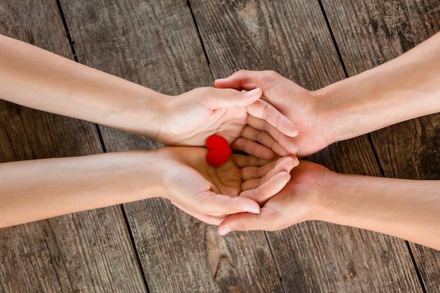 Mains mâles et femelles tenant un coeur rouge sur fond en bois. Photo Premium