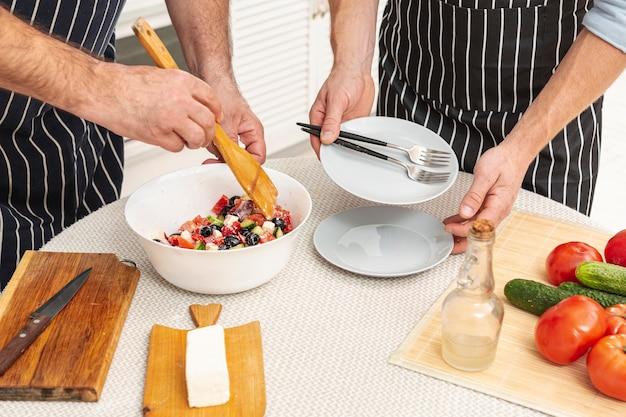 Mains mâles préparant une délicieuse salade Photo gratuit
