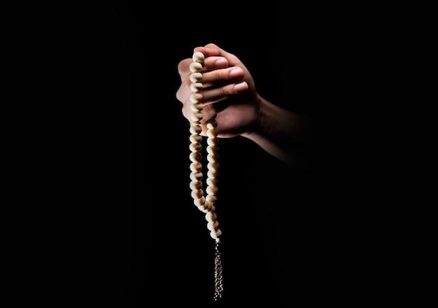 Mains mâles priant avec des perles de prière Photo Premium