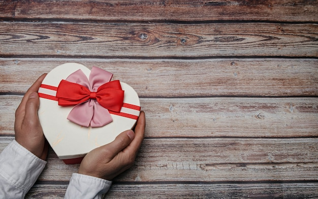 Mains Mâles Tenant Une Boîte-cadeau En Forme De Coeur Avec Des Nœuds Papillon. Thème De La Saint-valentin. Concept Lgtbi Photo Premium