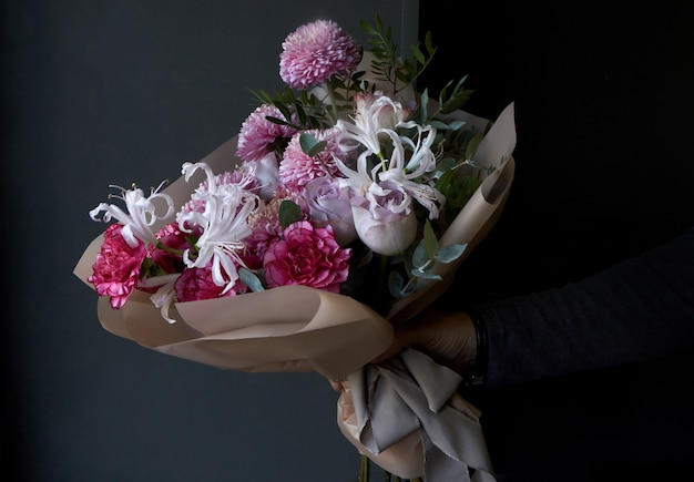 Mains mâles tenant un bouquet décoré dans un style vintage sur un fond sombre Photo Premium