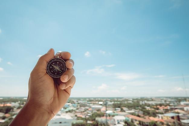 Mains mâles tenant une boussole dans le ciel Photo Premium
