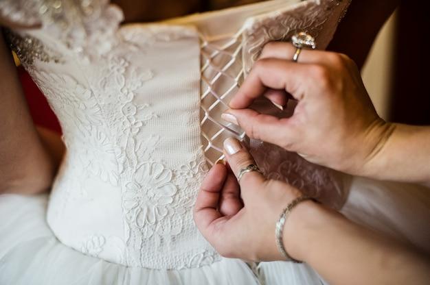Les mains de maman nouent le corset de la robe de mariée de la mariée Photo Premium