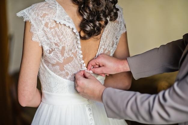 Les mains de maman nouent la robe de la mariée Photo Premium