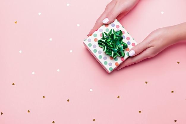 Mains Manucurées Femme Tenant Une Boite Verte Sur Fond Rose Pastel Avec Des Confettis Photo Premium