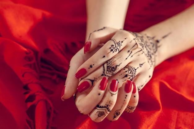 Mains manucurées rouges avec mehndi Photo Premium