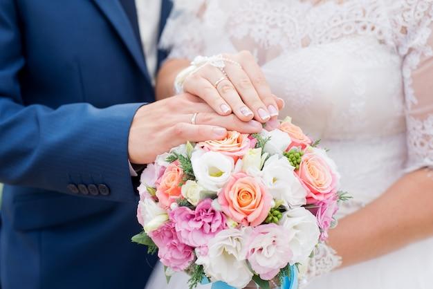 Mains, de, marié, mariée, à, alliances, et, bouquet fleurs Photo Premium