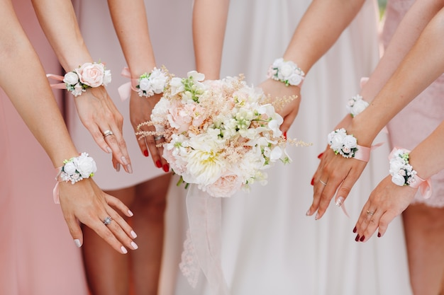 Mains de la mariée et demoiselles d'honneur avec des fleurs à l'ombre rose Photo Premium