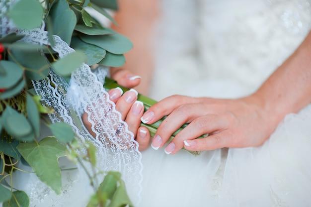 Les mains d'une mariée, juste marié, un bouquet de mariée est à côté Photo Premium