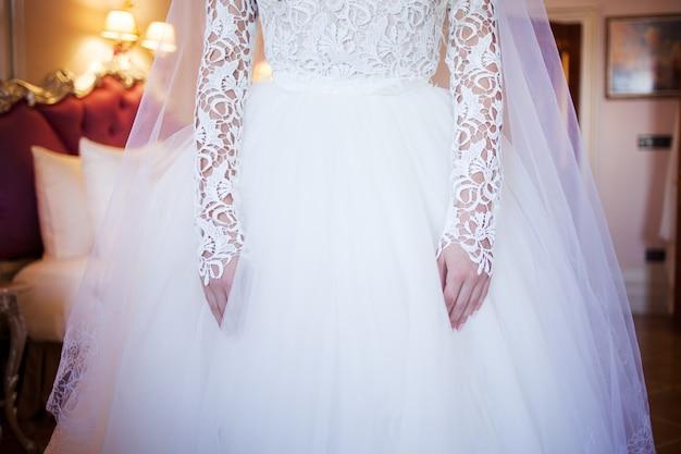 Mains mariée avec manucure. poignet sur le fond de la robe de dentelle blanche recouverte d'un voile Photo Premium