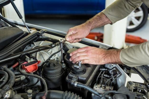Mains de mécanicien entretien d'une voiture Photo gratuit