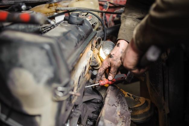 Mains de mécanicien réparateur travaillant sur le moteur à l'aide d'un outil Photo Premium
