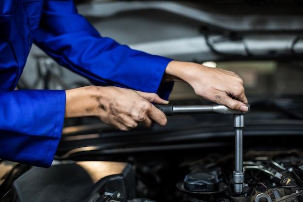 Mains de mécanicienne entretien d'une voiture Photo gratuit