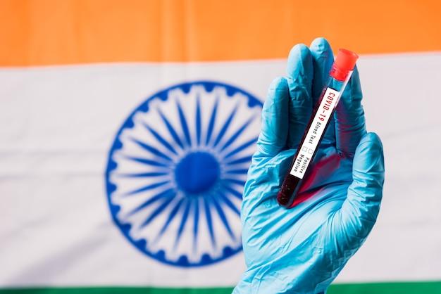 Mains D'un Médecin Portant Des Gants Tenant Le Virus Du Coronavirus Du Tube à Essai Sanguin (covid-19) Dans Le Laboratoire Sur Le Drapeau Inde Photo Premium