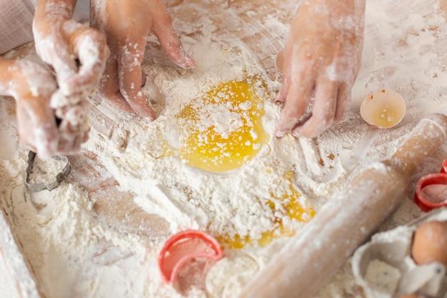 Les mains mélanger de la farine et des oeufs pour la pâte Photo gratuit