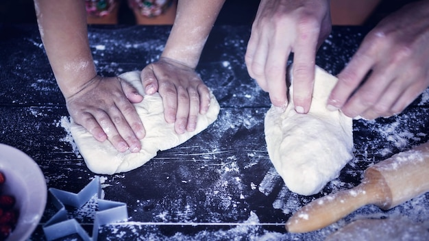 Des mains de mère et fille pétrir la pâte sur une table en bois. préparation au four Photo Premium