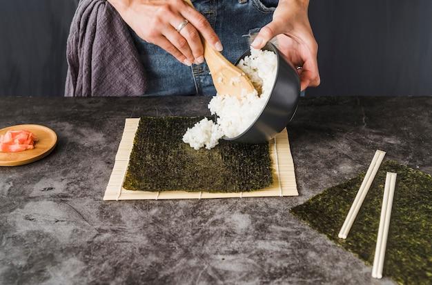 Mains mettant du riz sur des algues grillées Photo gratuit