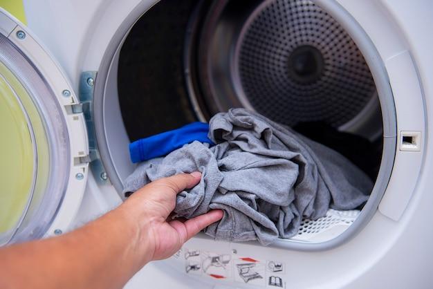Les mains mettent les vêtements dans la machine à laver Photo Premium
