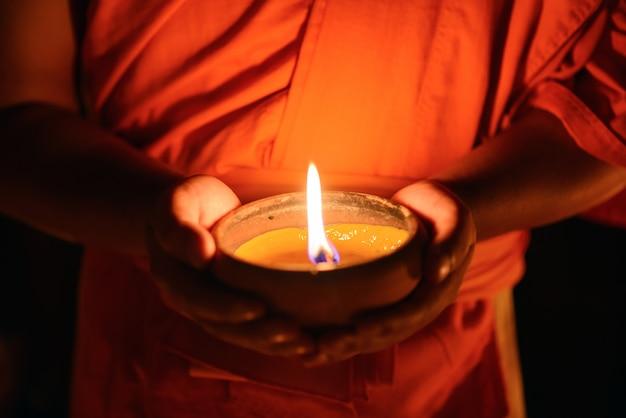 Mains moine bouddhiste tenant la coupe de bougie dans l'obscurité, chiang mai, thaïlande Photo Premium