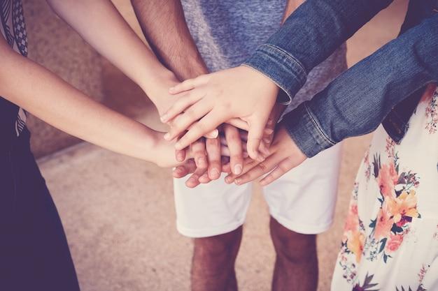 Mains multiethniques d'étudiants jeunes adultes rassemblant les mains, concept de travail d'équipe de bénévoles et de charité Photo Premium