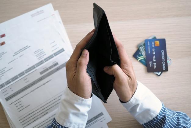 Les mains ouvrent le sac vide les factures et les cartes de crédit en attente de paiement Photo Premium