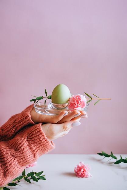 Mains peignant des oeufs de pâques de style moderne avec de la peinture rose Photo Premium
