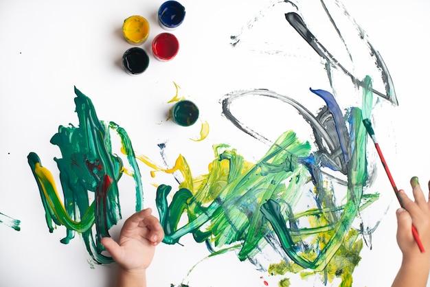 Mains D'un Petit Garçon En Train De Peindre à L'aquarelle Sur Une Feuille De Papier Blanc. Petit Garçon Avec Un Pinceau Et De La Peinture. Photo Premium