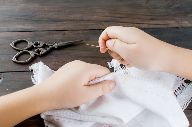 Les mains de la petite fille en train de broder une croix sur la toile. Photo Premium