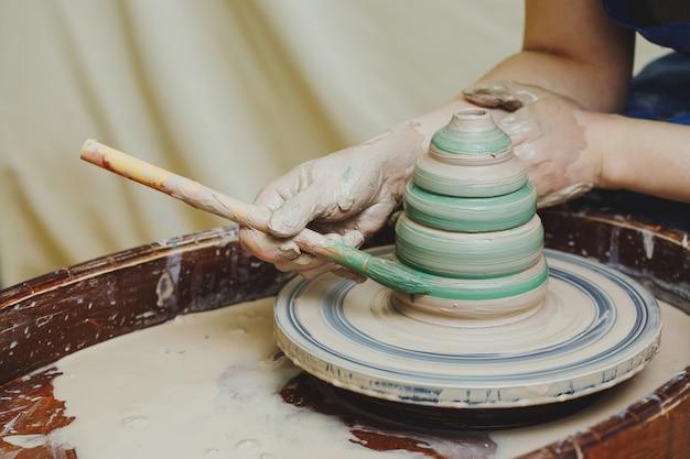 Mains Sur Potier. Artisan Artiste Peinture Pot Avec Pinceau Photo Premium