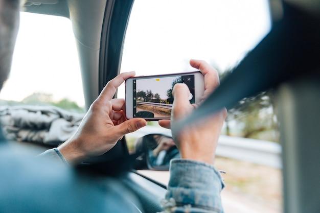 Mains prenant une photo au téléphone en voyage Photo gratuit