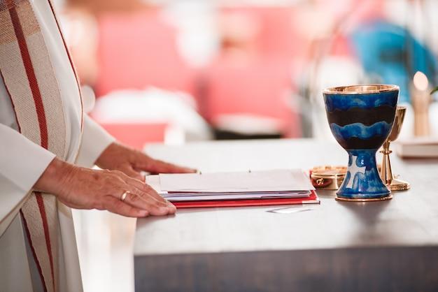 Mains, de, prêtre catholique, sur, autel, à, calice or, lecture, de, les, saint, livre Photo Premium