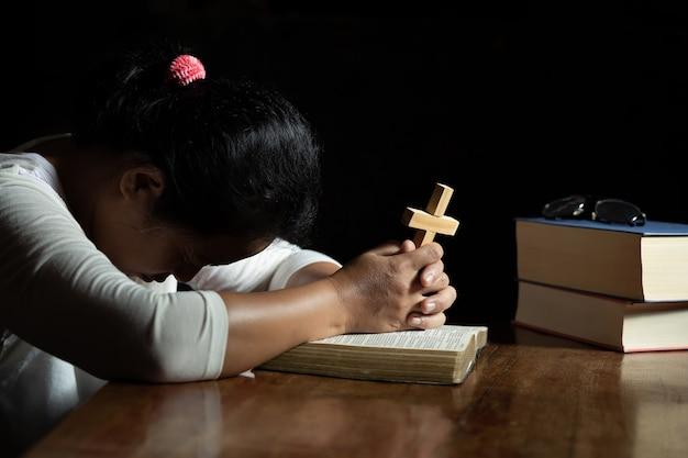 Mains priant dieu tout en tenant le symbole de la croix. Photo gratuit