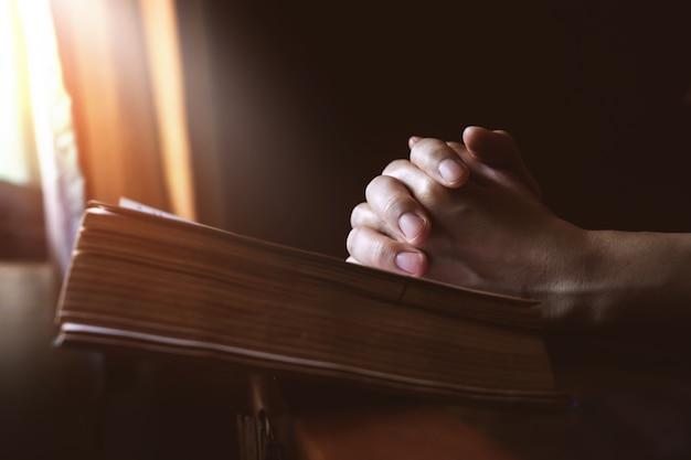Mains priant sur la sainte bible à côté d'une fenêtre Photo Premium