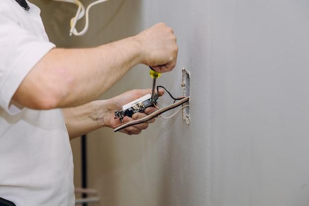 Mains professionnelles lors du montage du connecteur de prises électriques installé dans le placoplâtre de plaques de plâtre Photo Premium