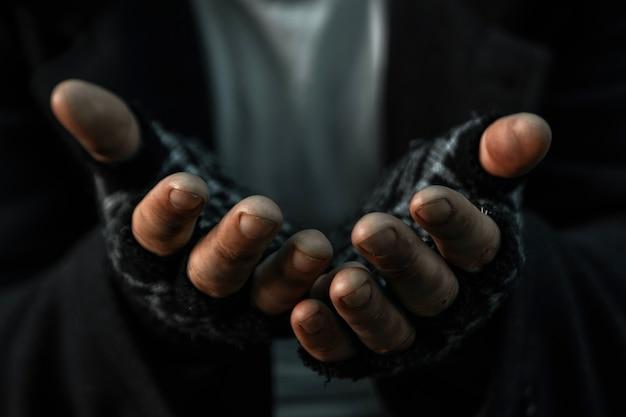 Les mains se bouchent pauvre vieil homme ou mendiant vous demandant de l'aide assis dans un bidonville sale Photo Premium