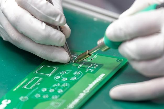 Les mains soudent des composants sur une carte de circuit imprimé en utilisant du cuivre et un fer à souder. Photo Premium
