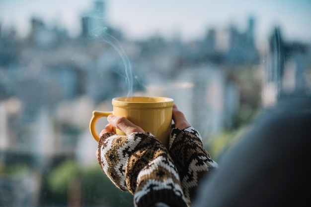Mains avec tasse de boisson chaude Photo gratuit